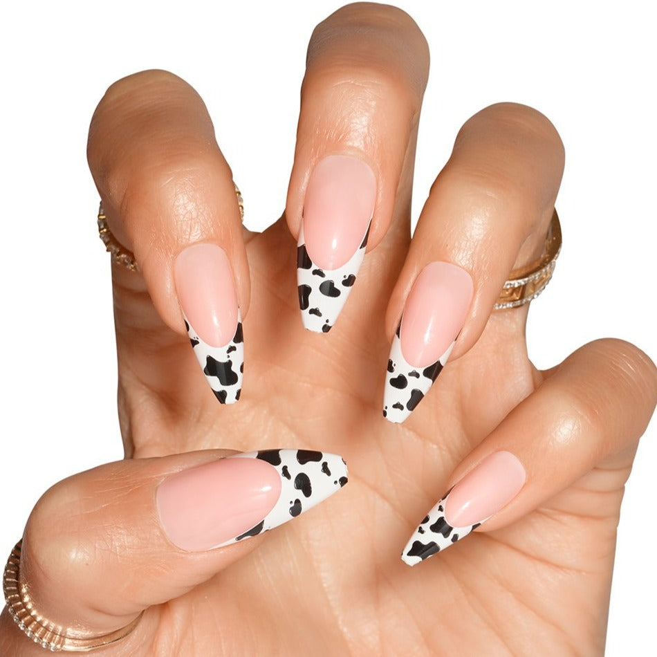 Claw hand wearing Big Moood nails, natural french with cow print on tip, in ballerina shape