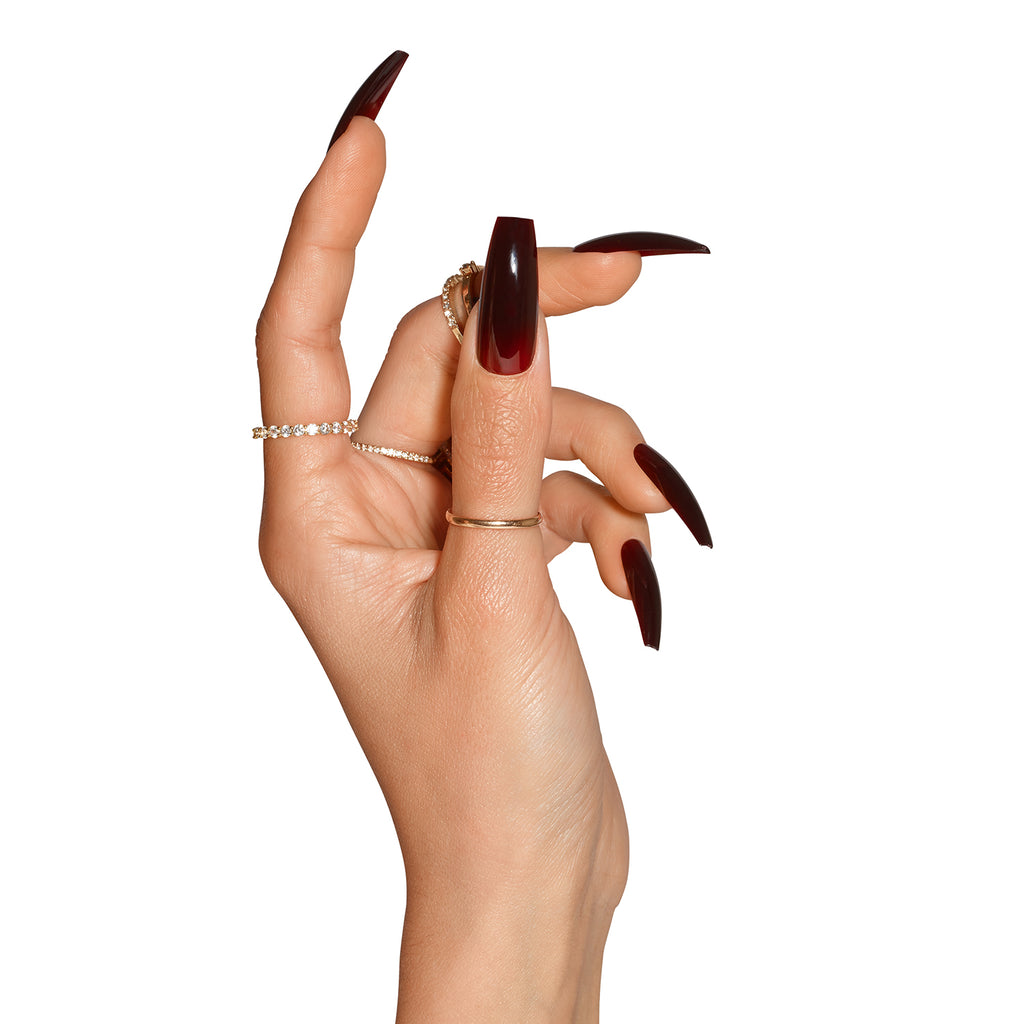 Side view of hand wearing Tres She Cherry Cola dark red jelly nails in coffin shape ultra long length
