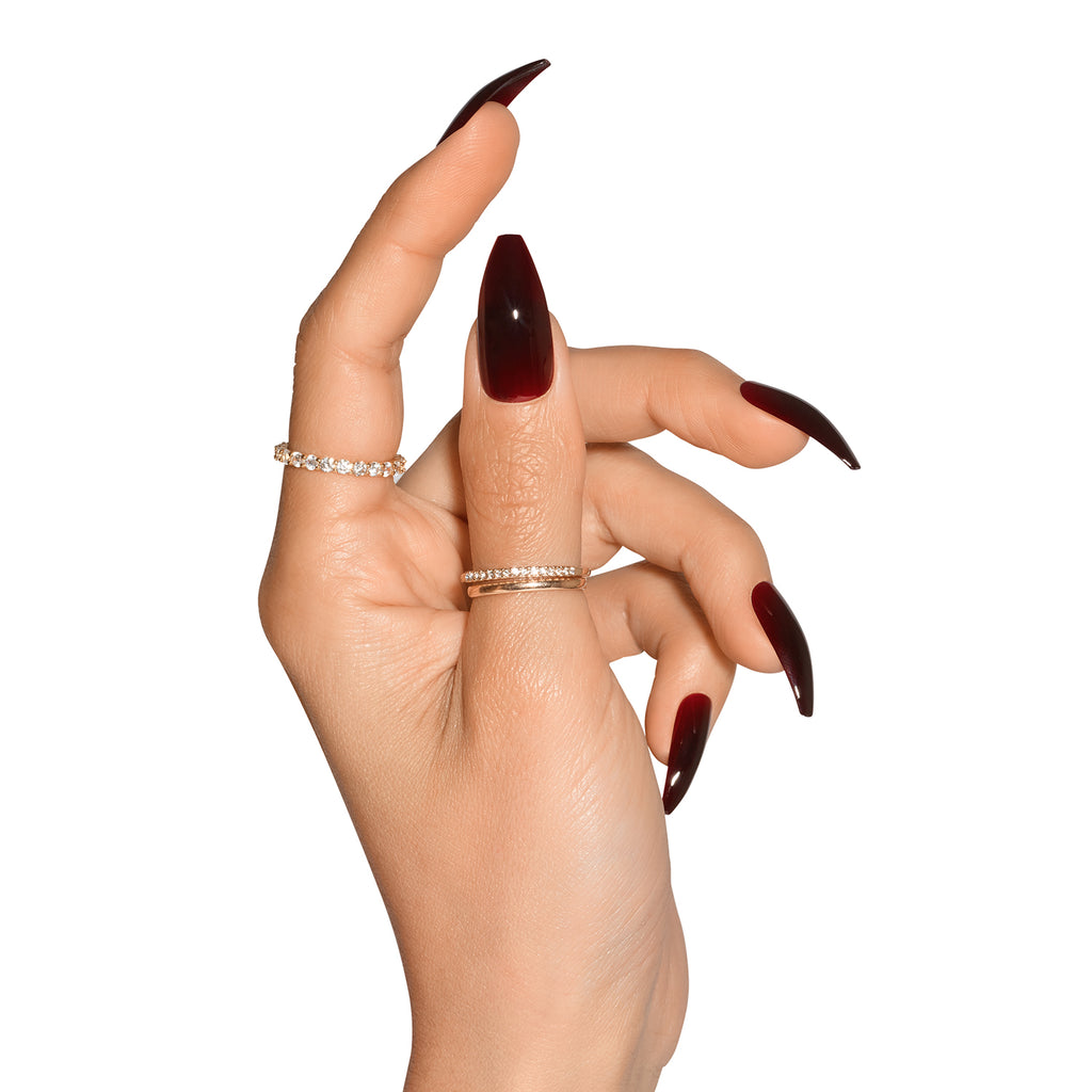 Side view of hand wearing Tres She Cherry Cola dark red jelly nails, ballerina shape long length