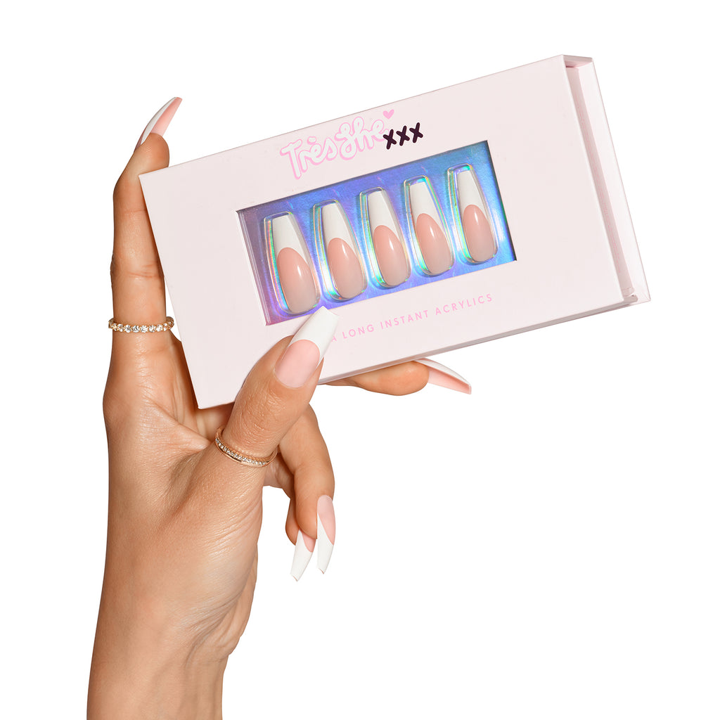 Hand wearing Porn Star nails, holding box with natural french tip, in coffin shape ultra long length inside