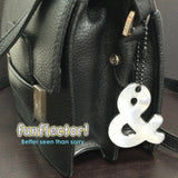 Stylish black ampersand safety reflector on a black purse.