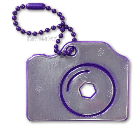 Purple camera pedestrian safety reflector for camera bags and backpacks.