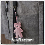 Pink teddy bear safety reflector on gray backpack by funflector