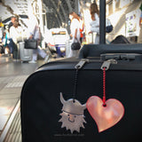 Viking and heart safety reflector on suitcase at train station