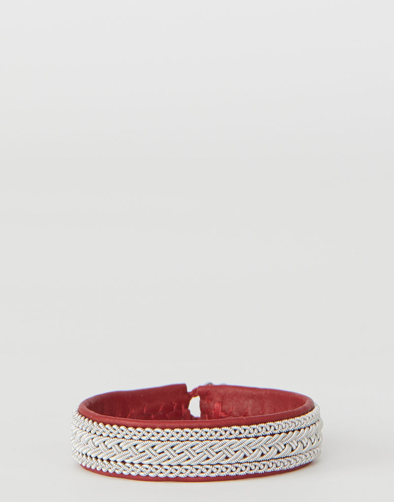 The B35 Red Leather & Pewter Embroidered Bracelet by Maria Rudman is handmade in Sweden and designed to patina with age. The pewter embroidered leather bracelet combines the ancient technique of pewter embroidery with hand sewn leather. The inside of the bracelet is hand stitched closed. Fasten with a simple horn button closure and branded silver tag. Wear this one-of-a-kind piece wherever you go and see it age with elegance..jpeg