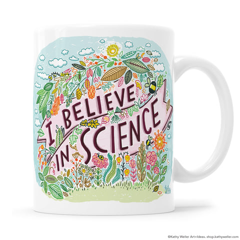 "I Believe In Science is a cute mug with a serious message! Sweet nature illustration anchored with an ""I Believe In Science"" banner in the center. Designed by Kathy Weller Art."