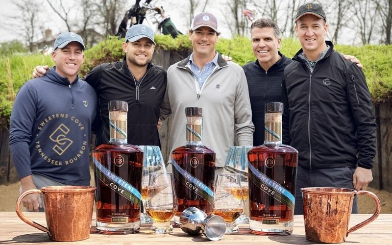 Nolan, Roddick, Collins, Rivers, and Manning with a table of their bourbon - Image by insidehook.com