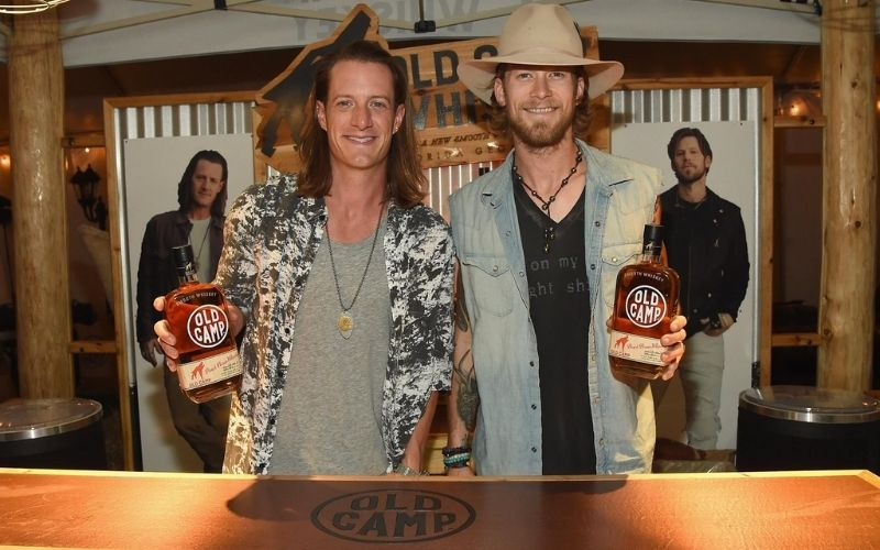 Hubbard and Kelley holding a bottle of Old Champ Bottle - Image by Old Camp Whiskey