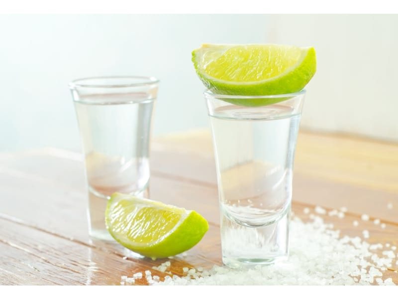 Tall shot glasses with liquor and lime slices