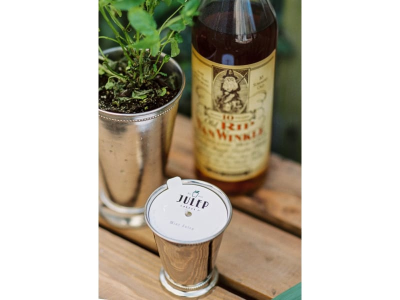 Mint Julep Candle, a plant, and liquor on a wooden table