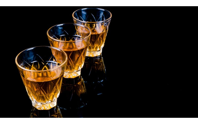 Three clear glasses with scotch