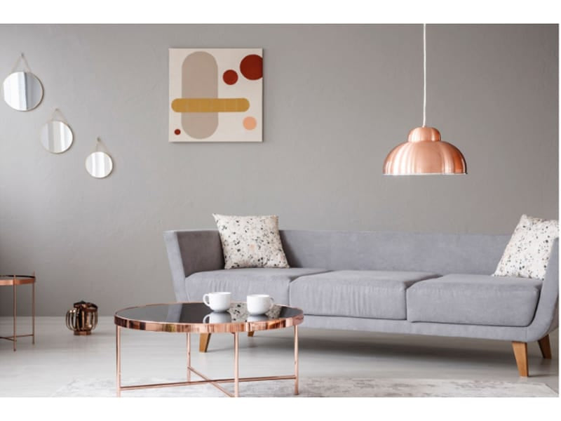 Copper lamp and coffee table in front of a modern sofa in a grey living room