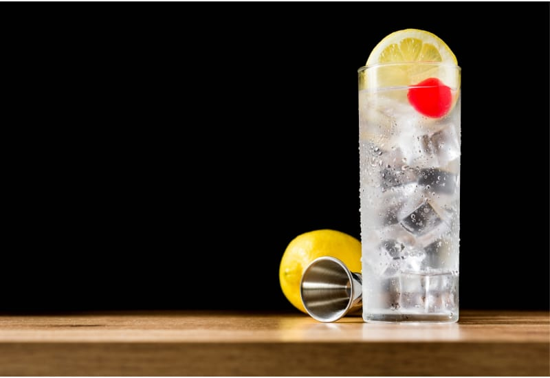 1 glass of Classic Tom Collins with lemon and jigger on the background