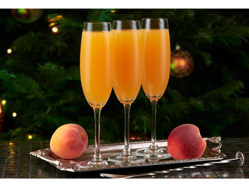 Three glasses of Baby Bellini with fresh peach fruits