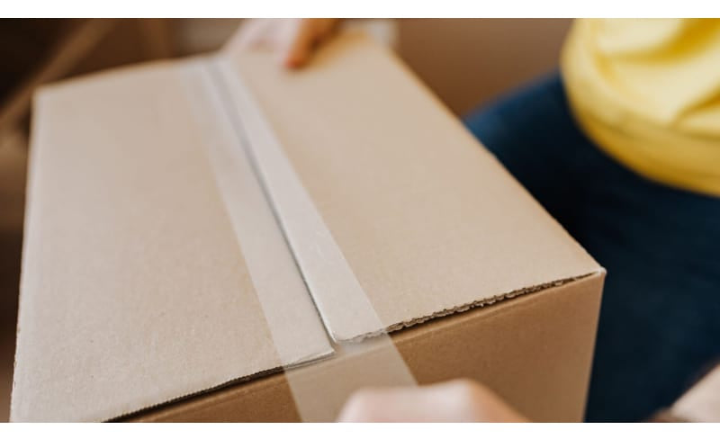 A person taping up a box