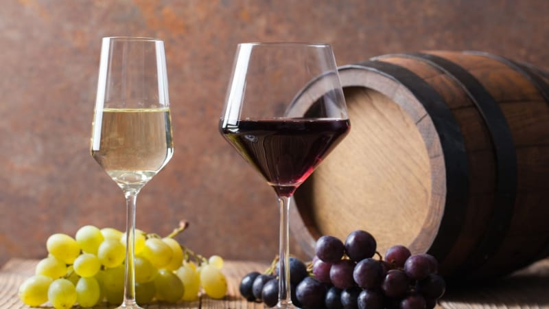 2 filled wine glasses with barrel and grapes on the table