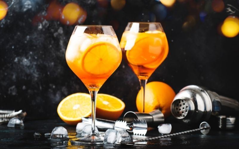2 glasses of Aperol Spritz cocktails with bar tools