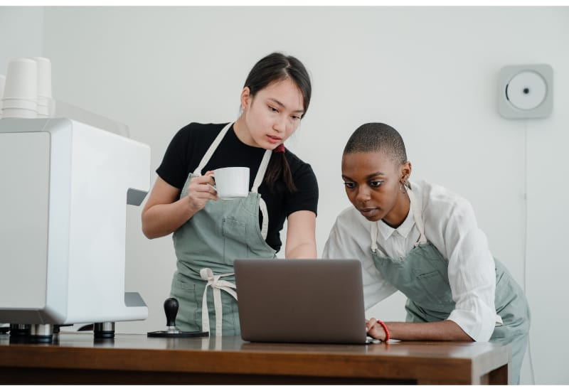 2 people in the kitchen looking up instructions on a laptop