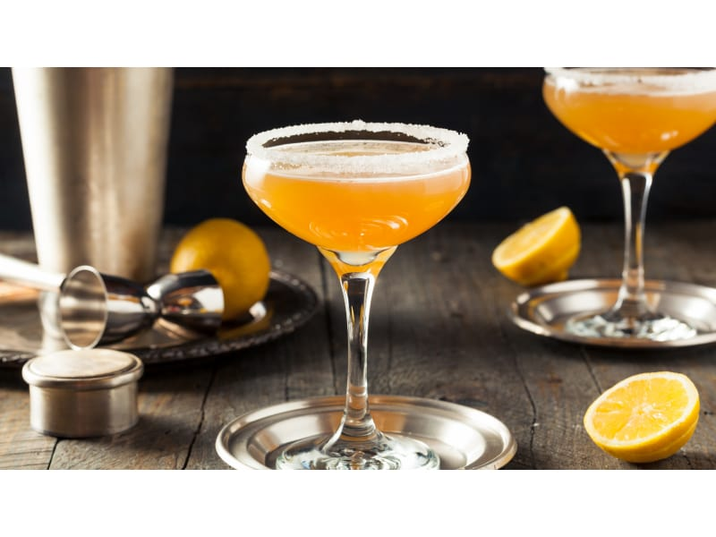 Bright yellow drink with lemons and bar tools