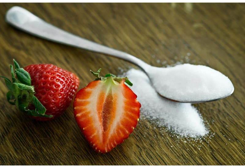 2 strawberries (one whole and one sliced) laid beside a teaspoon full of sugar