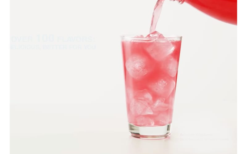 Red carbonated drink being poured into a glass