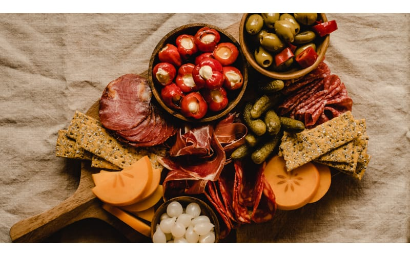 Wooden platter containing biscuits, cheese, fruits, and meat