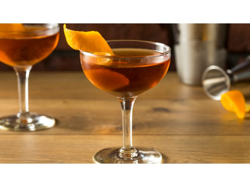 Two glasses of bronze drink with an orange twist