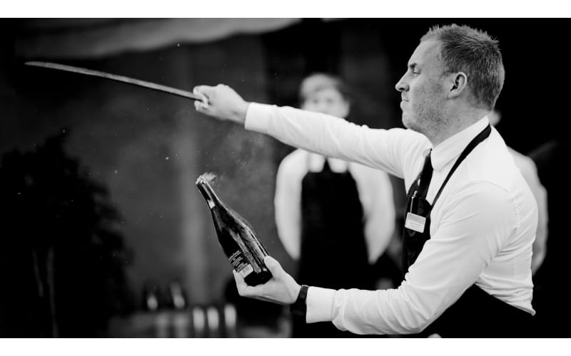 Man opening a bottle with a sword