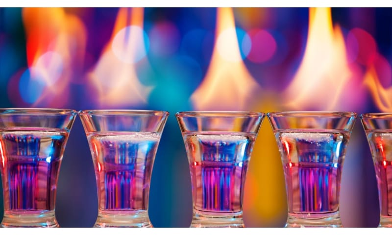 5 flamed shot glasses with colorful background