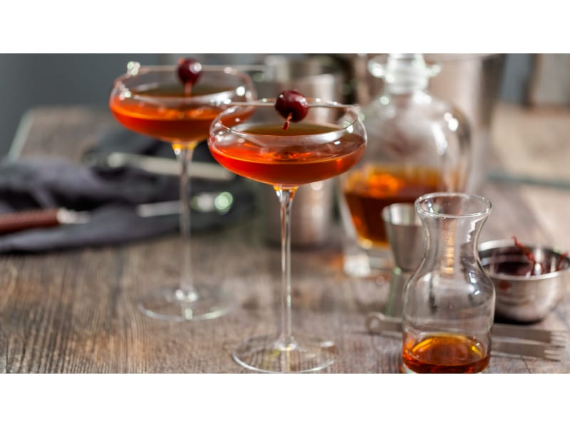 Reddish-brown cocktail with cherries