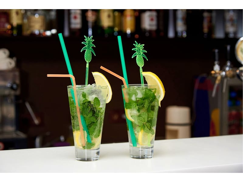 Mojito with ice and bright straws on the bar