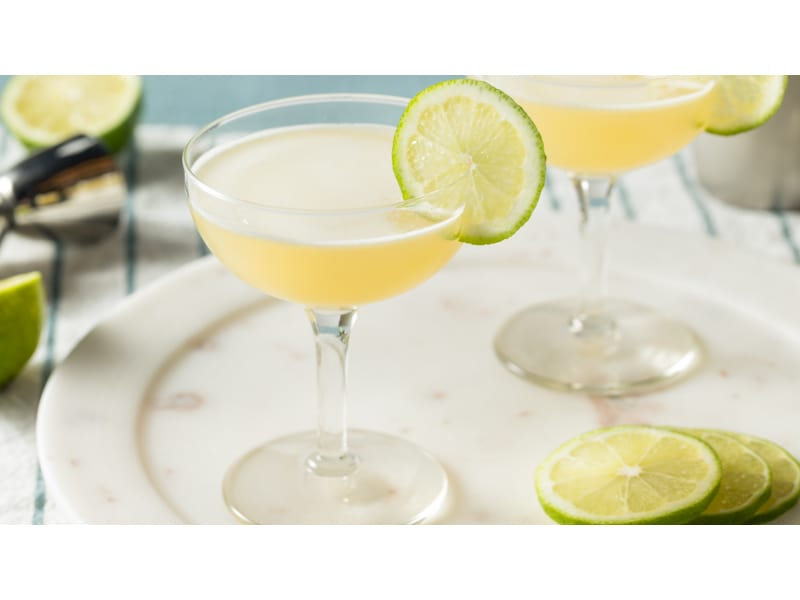 Light yellow drink with a lime wheel