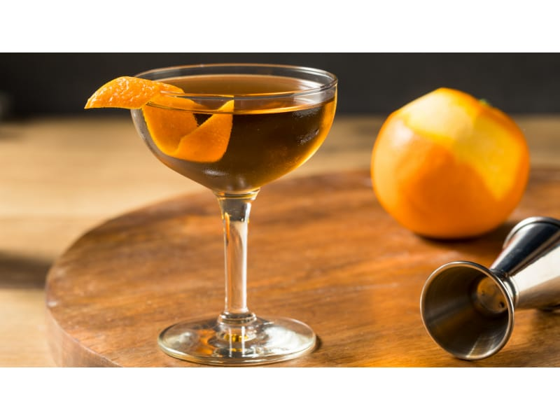 Gold drink with an orange twist and whole orange