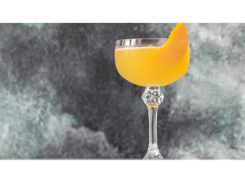 Yellow drink with an orange twist in gray background