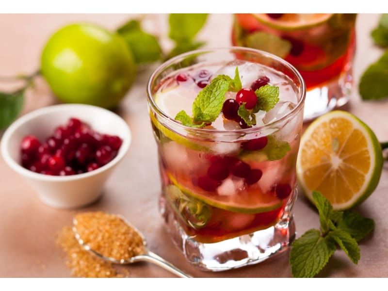 A glass of Virgin Cranberry Mojito with lime, berries, and sugar