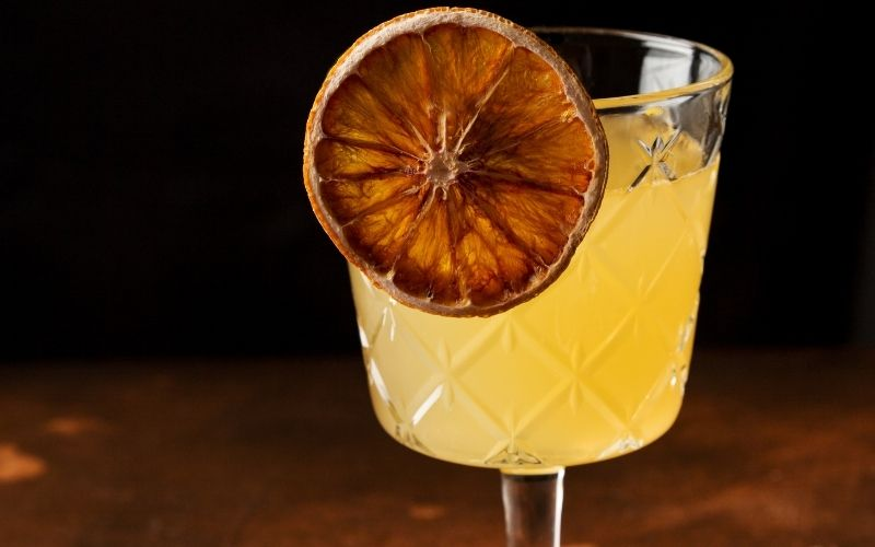 A dehydrated slice of orange in a cocktail glass