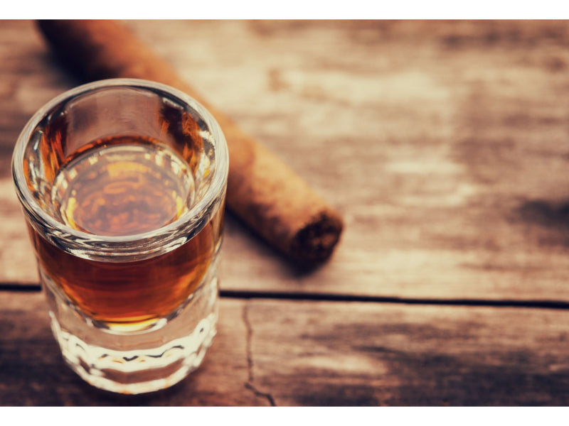 A glass of bourbon with a cinnamon stick