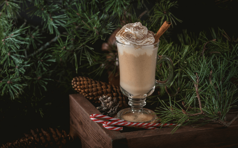A glass of eggnog cocktail with Christmas ornaments in the background