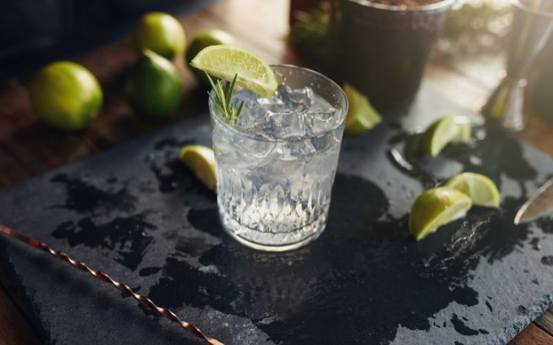 A glass of gin and tonic with limes in the background
