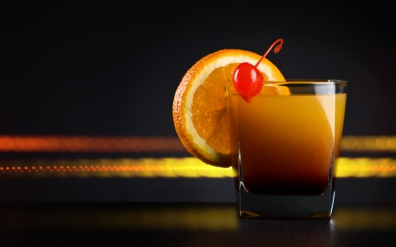 A glass of tequila sunrise on a dark background