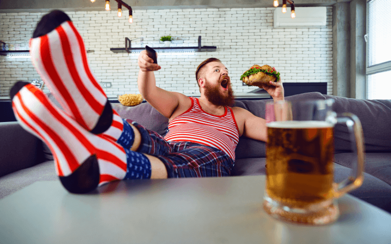 A man eating a burger with a glass of beer