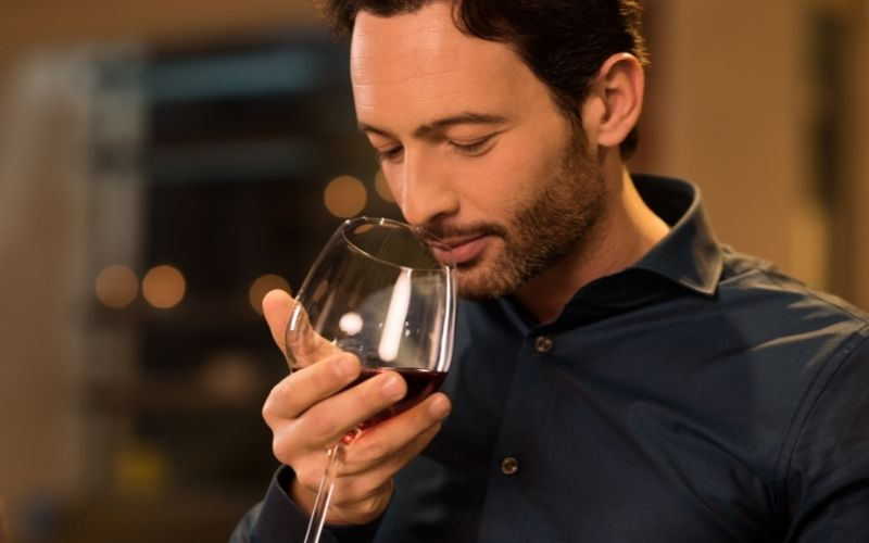 A man smelling a glass of red wine
