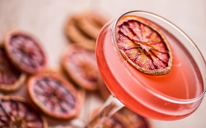 A pink cocktail garnished with dehydrated blood oranges