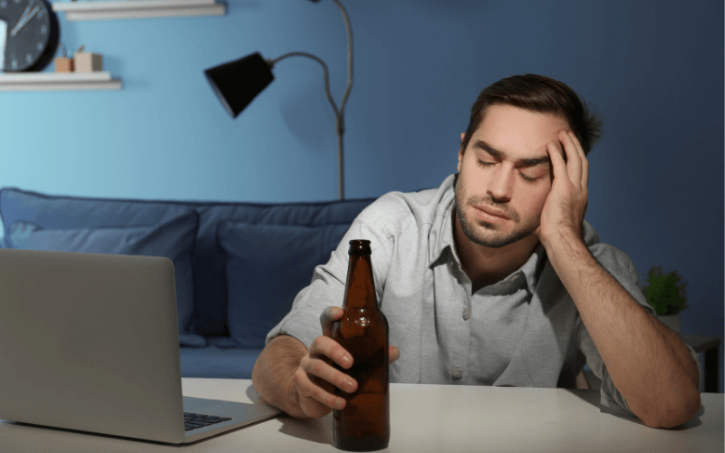 A tired and stressed man with a bottle of beer
