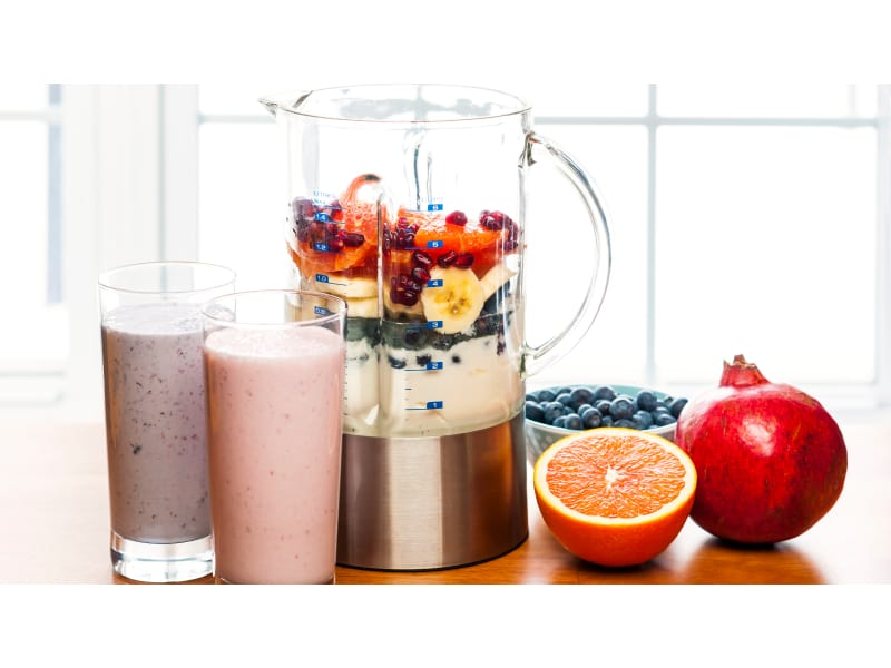Blender with smoothies and fruits on top of table