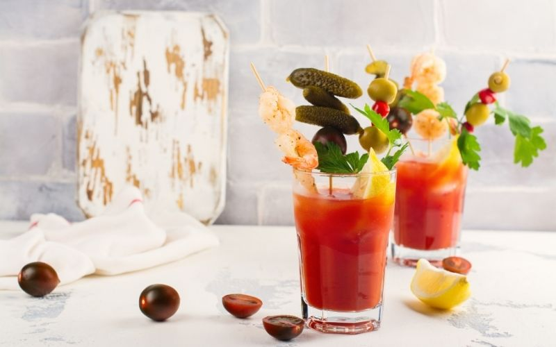 Bloody Mary cocktail garnished with skewered pickles and olives