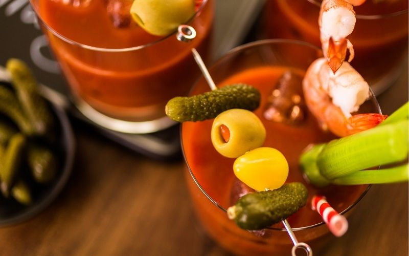 Bloody mary cocktail garnished with pickles and olives
