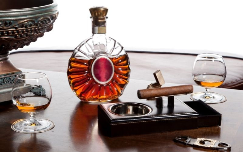 Bottle and glasses of Cognac with a cigar on a holder