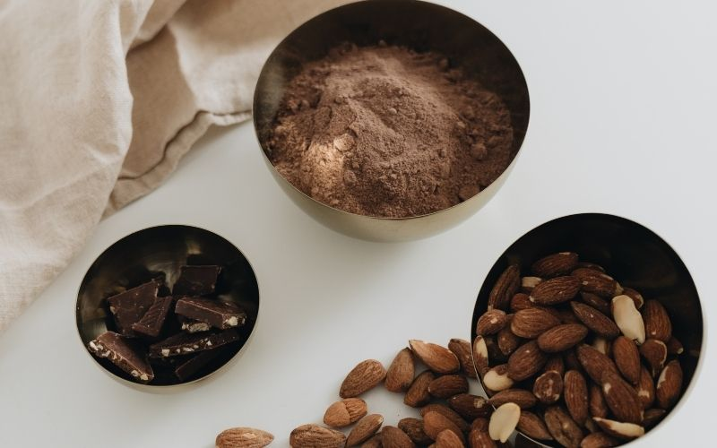 Bowls of cocoa powder, almonds, and chocolate