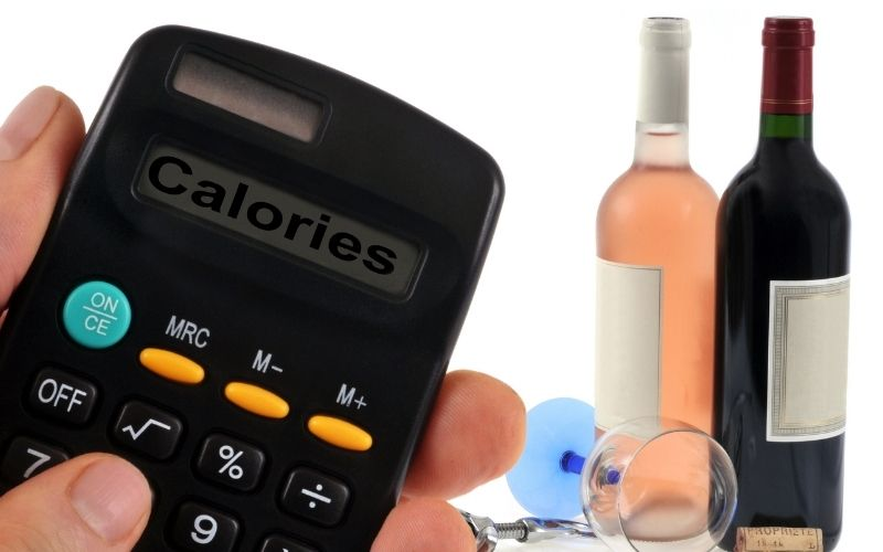 Calculator and wine bottles and glass behind